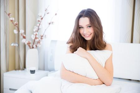 mujeres jovenes desnudas: Sensual mujer joven y sonriente sentado en la cama y abrazando la almohada blanca