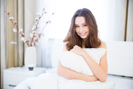 naked young women: Sensual smiling young woman sitting on bed and hugging white pillow