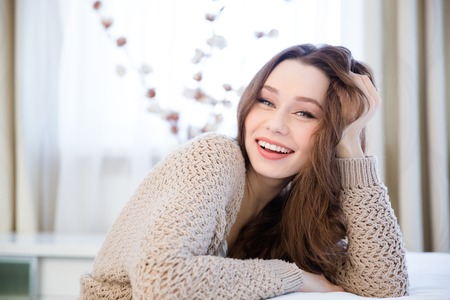 knitted jacket: Happy lovely relaxed young woman in beige knitted jacket sitting at home