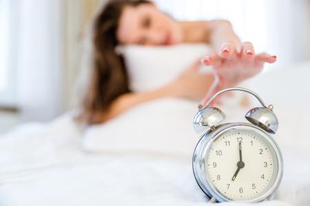 oversleep: Sleepy woman trying to turn off the alarm clock. Focus on alarm Stock Photo