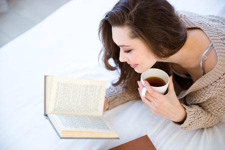precioso libro de lectura de la mujer joven linda y beber café en la cama