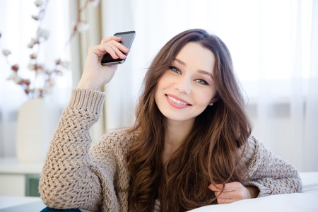 knitted jacket: Attractive happy young woman in beige knitted jacket sitting and holding smart phone at home Stock Photo