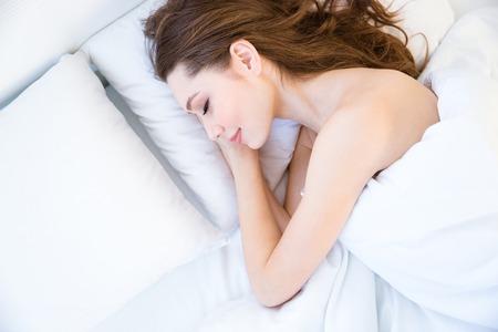 jeune fille adolescente nue: Vue de dessus fatigu� belle jeune femme aux cheveux longs dormir sur le lit dans la chambre Banque d'images