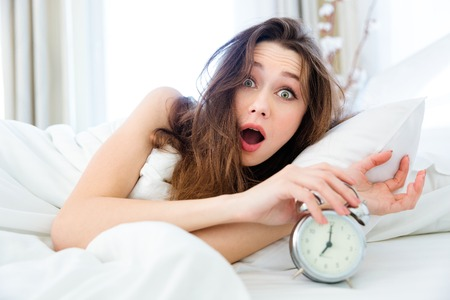 awaken: Shocked young woman waking up with alarm