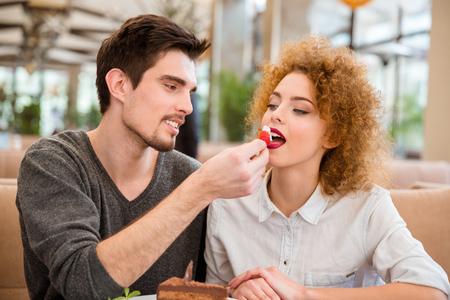 Portrait eines glücklichen Paar essen Kuchen mit Erdbeere im Restaurant