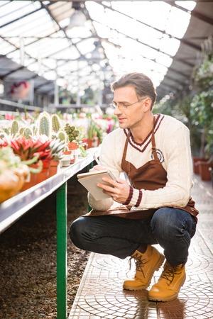 Knappe man tuinman kijken naar cactussen en notities maken in notitieboekje in orangerie