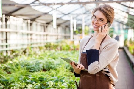smiling woman in a greenhouse: Smiling young woman gardener in uniform and glasses using mobile phone and tablet in greenhouse