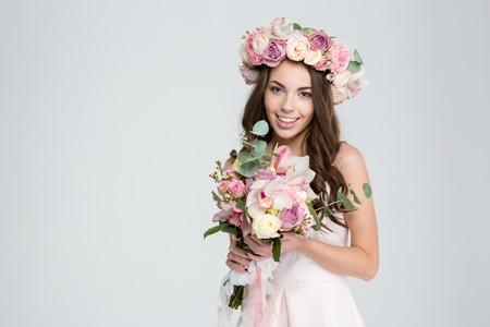 Charmante jonge bruid in bloemen krans en witte jurk met mooi boeket