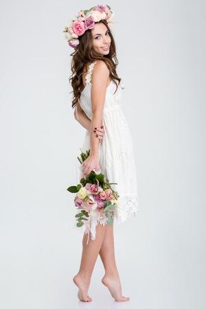 mujer con rosas: Longitud total de mujer joven y sonriente en traje blanco y una corona de rosas de pie descalzo con el ramo de flores