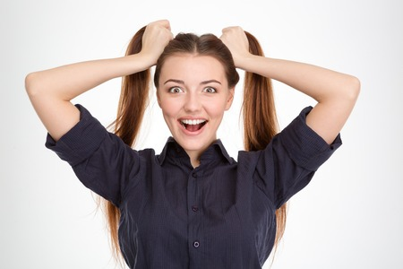ponytails: Funny excited young woman with two ponytails holded by hands over white background