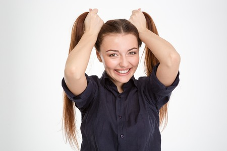 ponytails: Cheerful beautiful young woman making two ponytails by hands over white background
