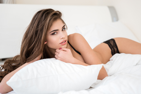 erotic breast: Portrait of a lovely woman in lingerie lying on the bed and looking at camera
