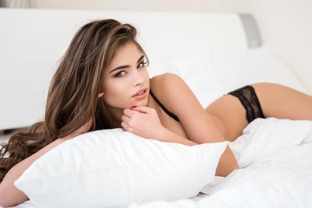 pechos: Retrato de una mujer hermosa en ropa interior acostada en la cama y mirando a la cámara Foto de archivo