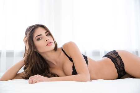 Pretty woman in sexy lingerie lying on the bed and looking at camera Stock Photo