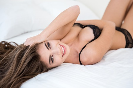 sexy breasts: Smiling sexy woman in lingerie relaxing on the bed Stock Photo