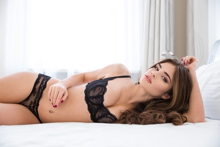 breast beauty: Portrait of a charming sexy woman in lingerie lying on the bed and looking at camera