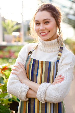 smiling woman in a greenhouse: Smiling pretty woman gardener in white sweater and striped apron standing with arms crossed in greenhouse Stock Photo