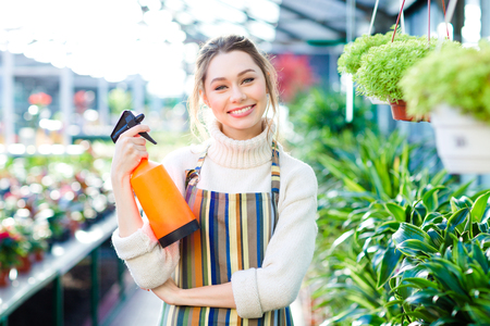 pulverizer: Cheerful attractive young woman gardener in colorful striped apron standing in orangery and holding water pulverizer Stock Photo