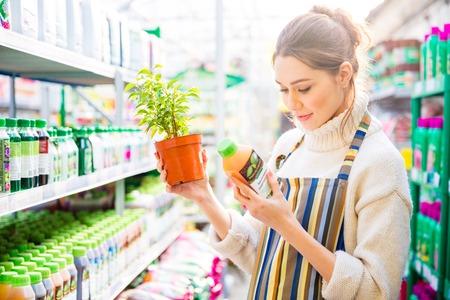 agricultura: Reflexivo bastante jardinero de la mujer de pie y leer acerca de los productos qu�micos agr�colas para flores y plantas en la tienda