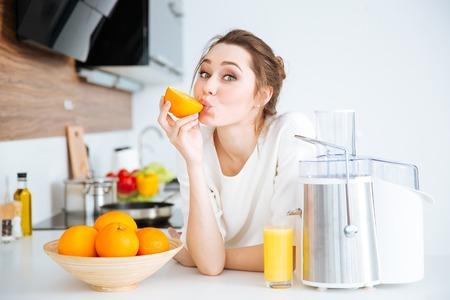 Giovane donna affascinante sveglia che produce succo e che mangia le arance sulla cucina