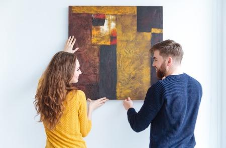若いカップルの自宅の壁に掛けられた絵