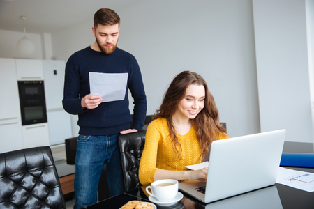 paying bills online: Portrait of a happy young couple paying their bills online with laptop at home