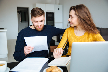 happy young woman: Happy young couple calculating bills at home Stock Photo