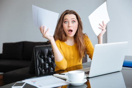 overrun: Amazed woman sitting at the table with bills at home Stock Photo