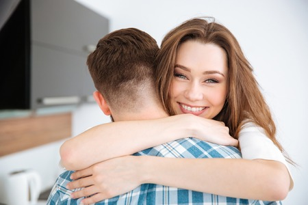 man woman hugging: Smiling young couple hugging at home