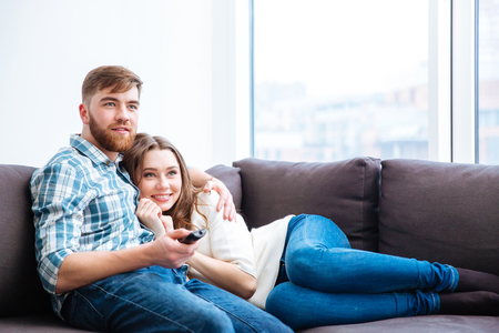 couple watching tv: Smiling young couple watching TV on the sofa at home Stock Photo