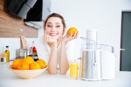 Beautiful happy woman using juicer for making orange juice in the kitchen Stock Photo