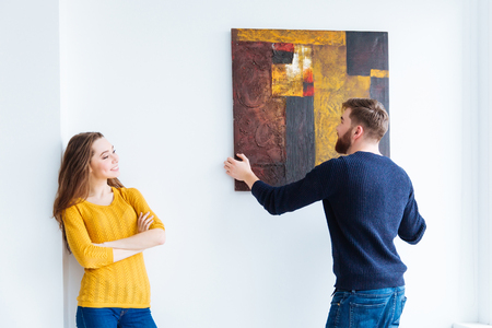 Young couple hanging picture on the wall at home