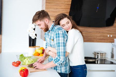 Tender woman hugging her husband while he cutting vegetables for salad on the kitchen