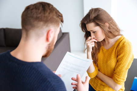 Worried couple discussing about domestic finances at home
