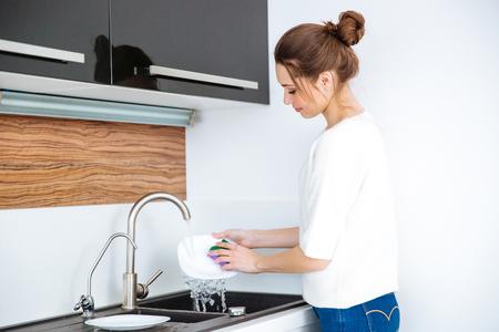 Śliczne piękne młode kobiety stojącej i mycia naczyń w domu