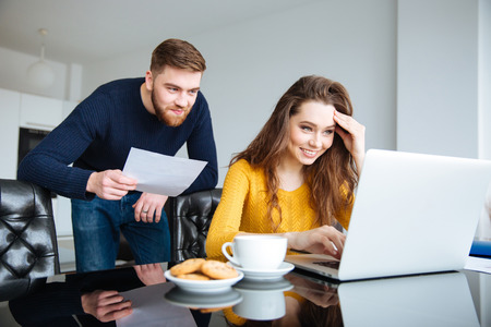 Portrait of a happy young couple calculating bills at home Stock Photo