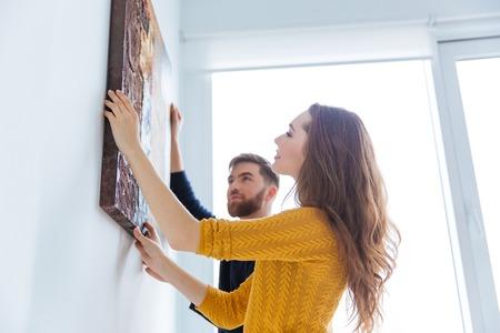 집에서 벽에 그림을 매달려 행복 한 커플