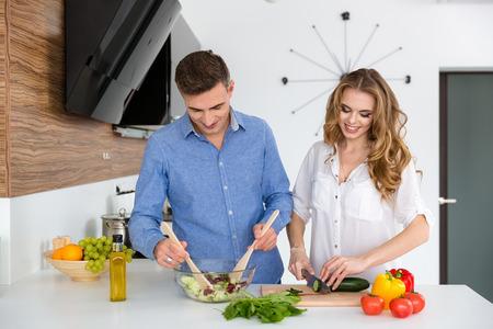 alimentacion sana: Hermosa pareja de pie y cocinar alimentos saludables juntos en la cocina