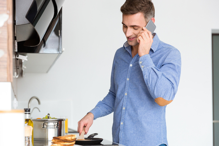 handsom: Happy handsome man talking on cell phone and frying pancakes on the kitchen