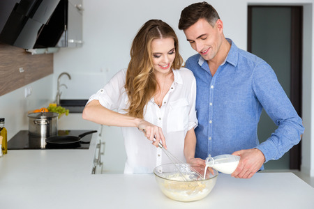 wife beater: Beautiful couple mixing products in glass bowl with hand beater on the kitchen Stock Photo