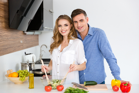 home cooking: Beautiful couple standing and cooking together on the kitchen at home