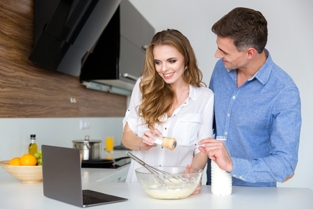 wife beater: Beautiful couple using laptop and cooking together on the kitchen Stock Photo