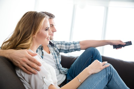woman watching tv: Profile of happy couple sitting on couch and watching tv together Stock Photo