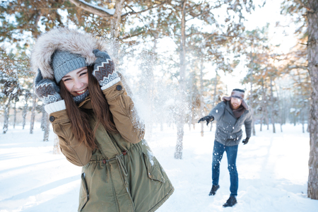 palle di neve: Beautiful happy couple throwing snowballs and having fun in winter park