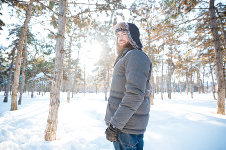 winter park: Portrait of cheerful attractive young man in warm clothes standing in winter park Stock Photo
