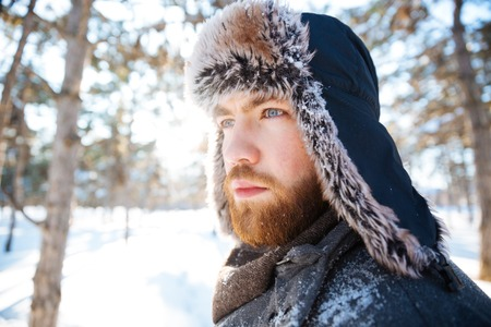 Closeup portrait of attractive thoughtful bearded young man in winter hat standing outdoors