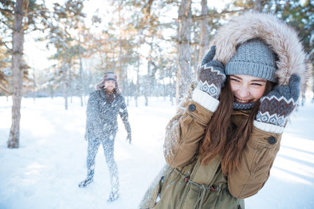 palle di neve: Happy young couple in winter clothes playing snowballs outdoors Archivio Fotografico
