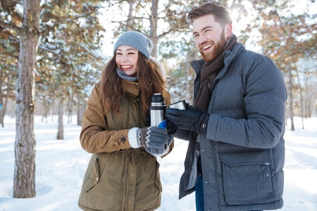 thermos: Laughing couple standing with thermos in winter park Stock Photo