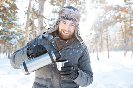 Happy attractive young man in warm jacket and hat drinking hot tea from thermos in winter park