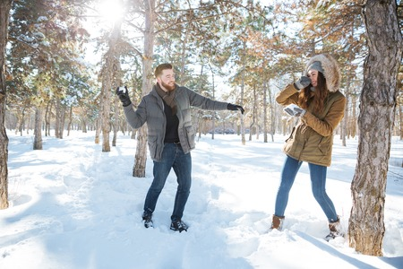 winter park: Happy couple playing with snow in winter park. Snowball fight